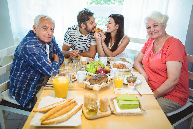 Happy couple having breakfast with their parents royalty free stock photos