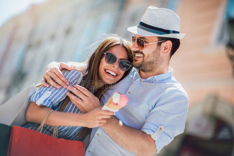 Couple having date and eating ice cream after shopping. Happy couple having date and eating ice cream after shopping stock photography