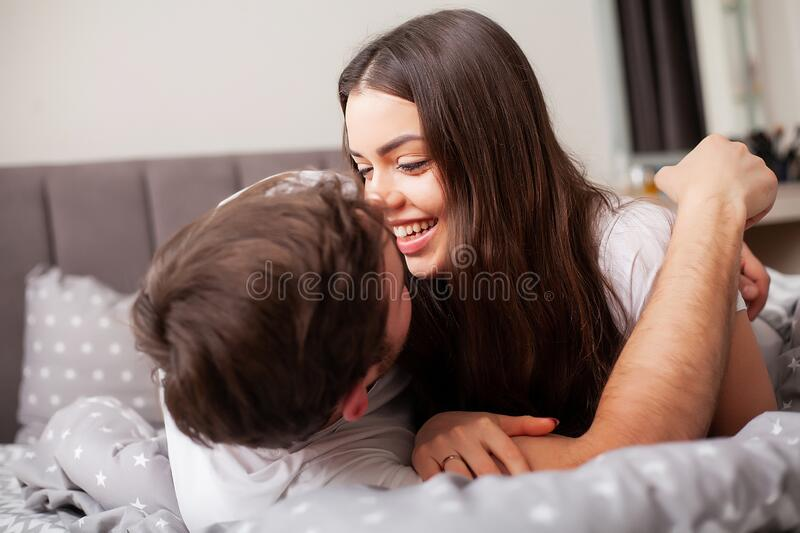 Happy couple having fun in bed. Intimate sensual young couple in bedroom enjoying each other stock images