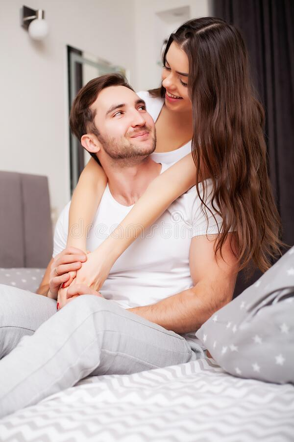 Happy couple having fun in bed. Intimate sensual young couple in bedroom enjoying each other royalty free stock photos