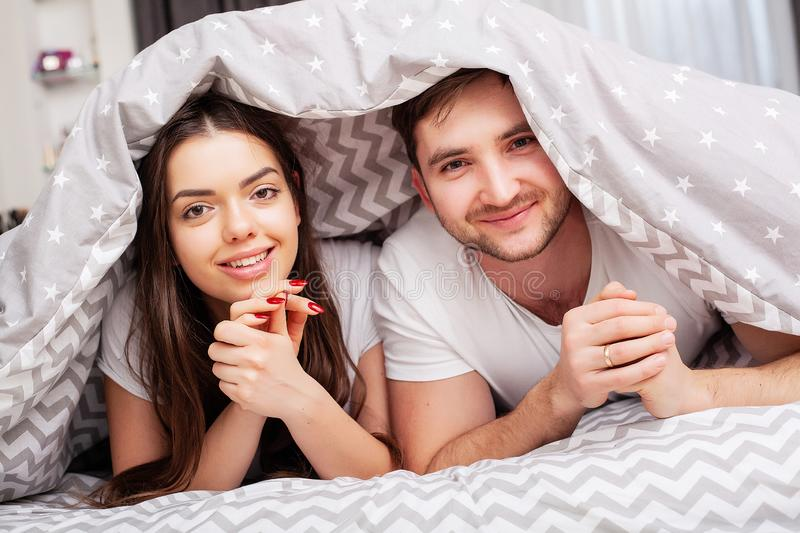 Happy couple having fun in bed. Intimate sensual young couple in bedroom enjoying each other royalty free stock photography