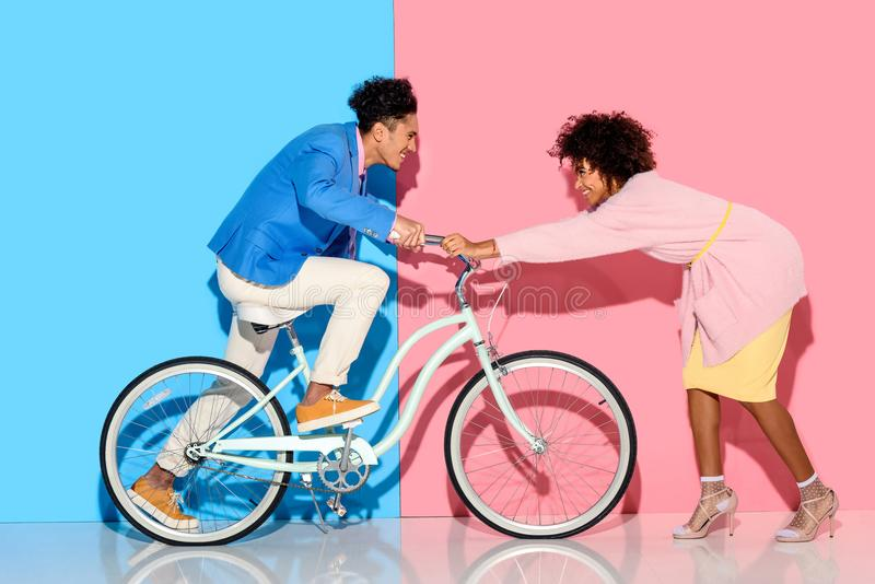 Happy couple having fun with bicycle on pink stock photo