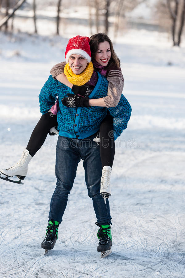 Happy couple having fun ice skating on rink outdoors. Winter sport and leisure concept. Love and fun in wintertime stock photos