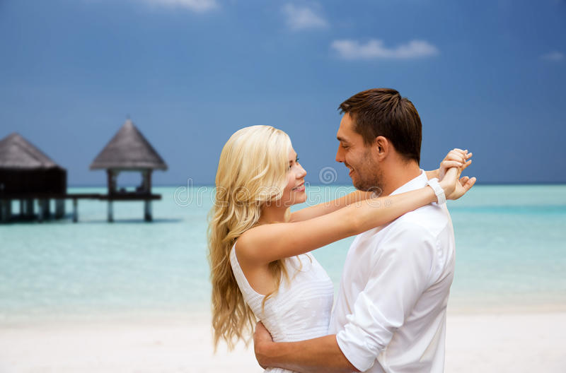 Happy couple having fun over beach with bungalow stock image
