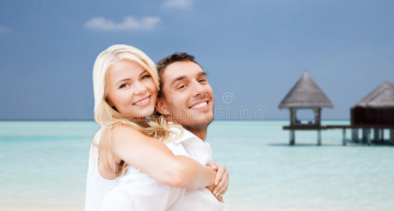 Happy couple having fun over beach with bungalow royalty free stock image