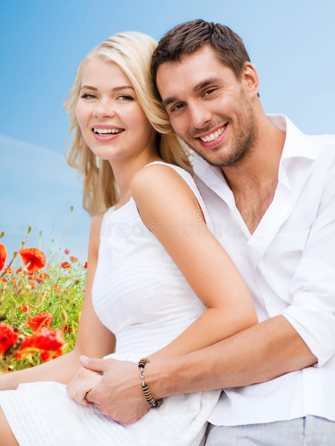 Happy couple having fun over poppy flowers field stock images