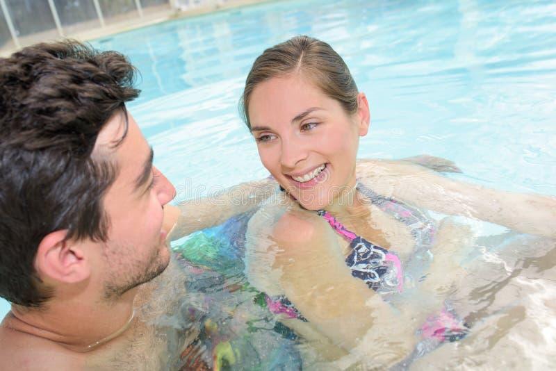 Happy couple having fun in pool royalty free stock image