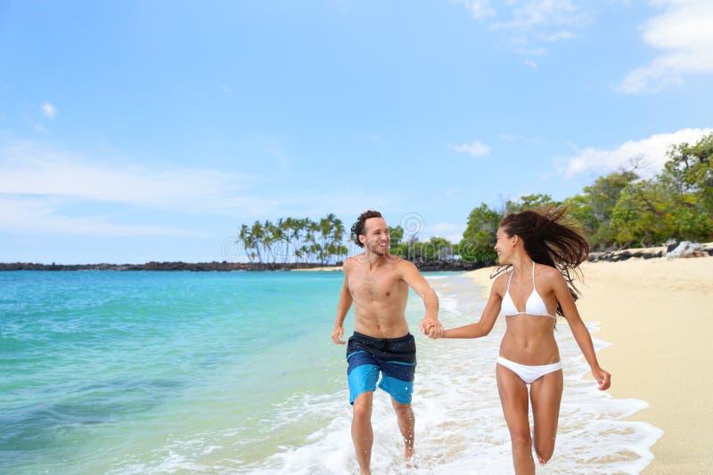 Happy couple having fun together running on beach stock photos