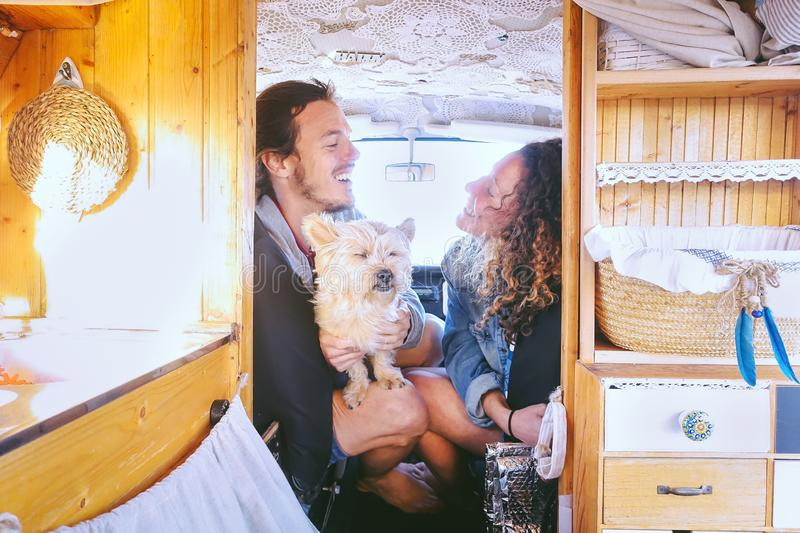 Happy couple having fun in vintage minivan with their dog during a road trip - Young people enjoying time together royalty free stock photography