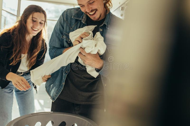 Happy couple having fun while washing clothes. Smiling men and women putting clothes in a washing machine together. Happy couple having fun doing laundry stock photo