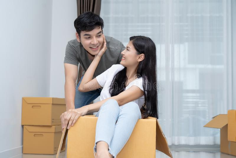 Happy couple having fun young man pushing young woman sitting on. Happy couple having fun young men pushing young women sitting on cardboard box in new house at stock images