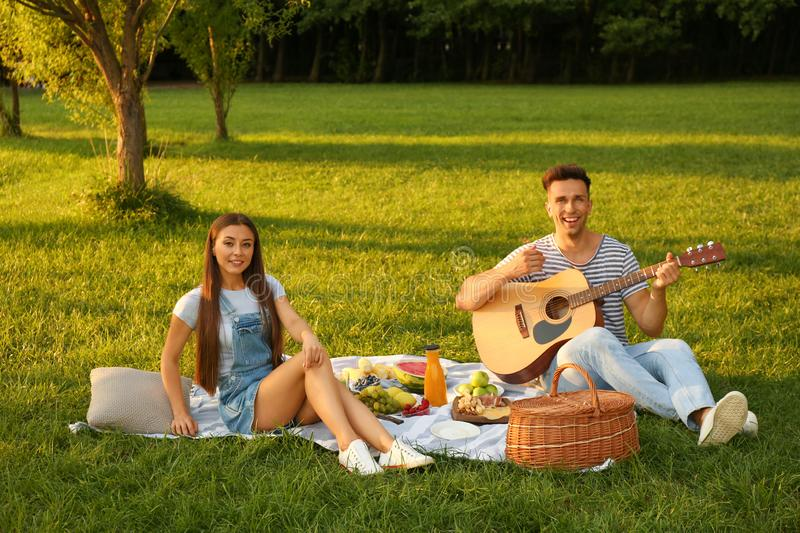 Happy couple having picnic on sunny day royalty free stock images