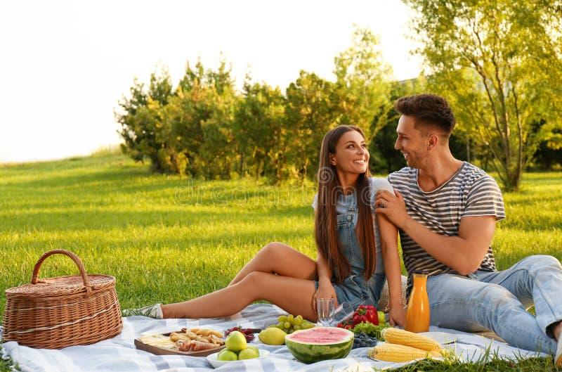 Happy couple having picnic on sunny day royalty free stock photography