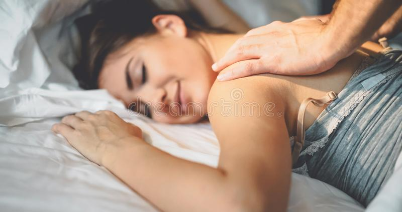 Happy couple having tender moments in the bed - Young romantic lovers intimate massaging and cuddling in the bedroom royalty free stock image