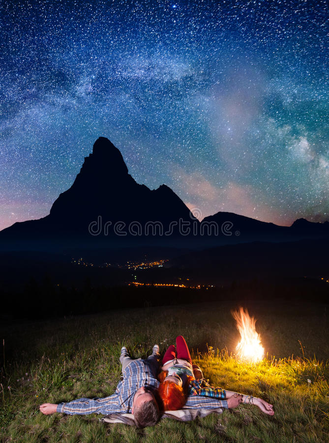 Happy couple hikers admiring the bright stars and lying near the fire at night. Long exposure royalty free stock photos