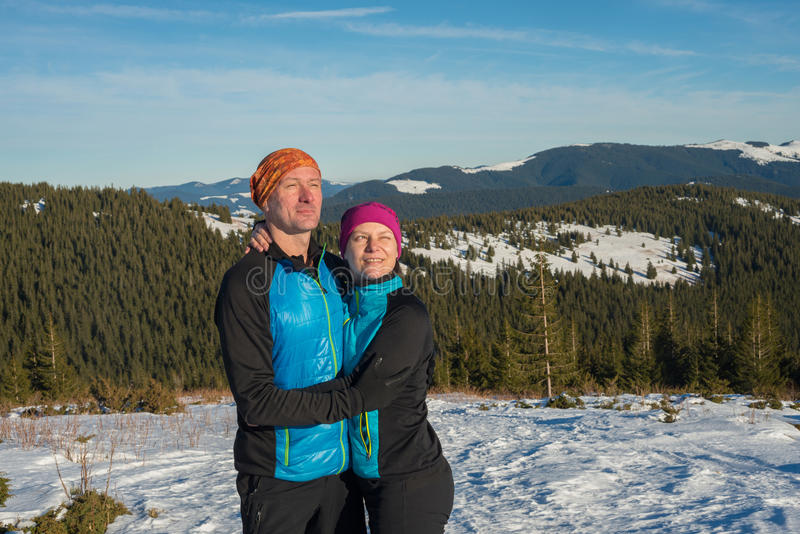 Happy couple hikers hugging and laughing during winter travel in royalty free stock images