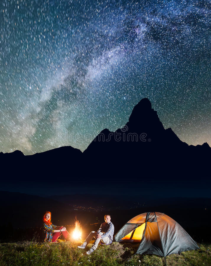 Happy couple hikers sitting near campfire and lighting tent under incredibly beautiful starry sky. Low light. Happy couple hikers sitting near campfire and stock photography