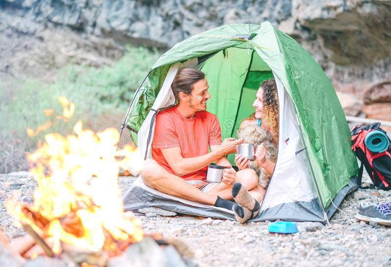 Happy couple of hikers with their dog camping with tent around rock mountains next to fire - People relaxing in a camp stock photos