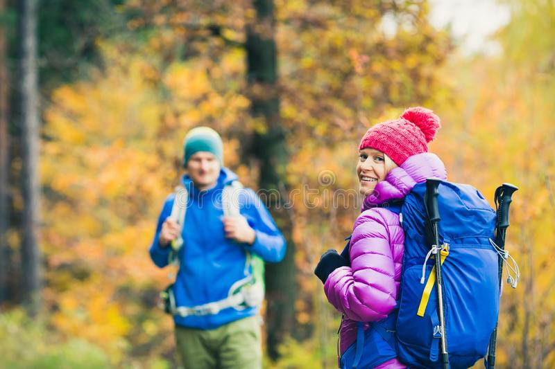 Man and woman happy couple hikers walking in autumn woods. Happy couple hikers trekking in beautiful yellow autumn forest and mountains. Young people men and stock photo