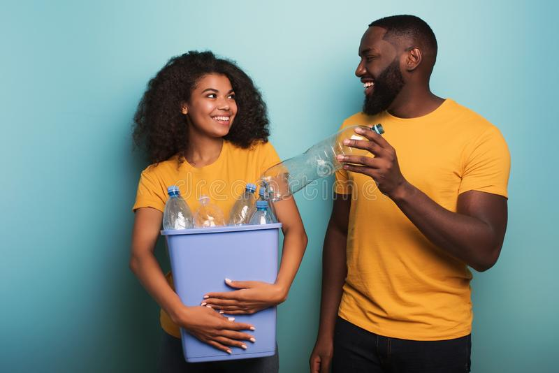 Happy couple hold a plastic container with bottles over a light blue color. Concept of ecology, conservation, recycling. Happy black couple hold a plastic royalty free stock photography