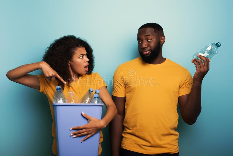 Happy couple hold a plastic container with bottles over a light blue color. Concept of ecology, conservation, recycling. Happy black couple hold a plastic royalty free stock image