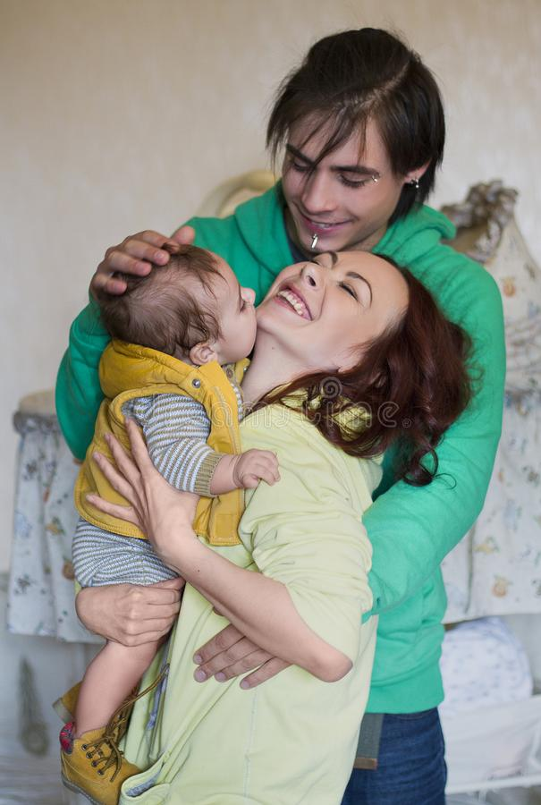 Young family mom, dad and son at home. Happy couple holding a baby, laugh happily. young neformal family with facial piercing. mom, dad and son at home royalty free stock photography