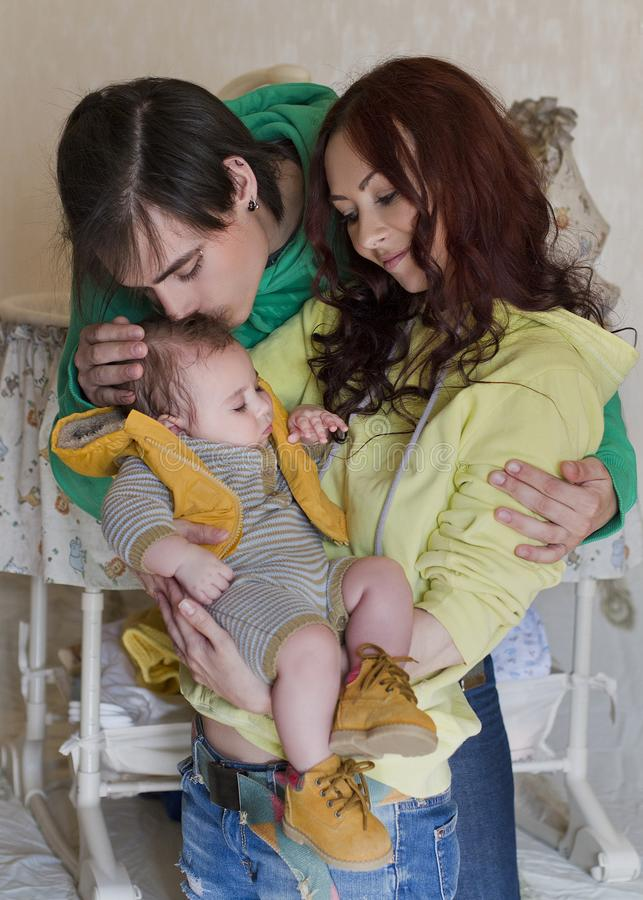 Young family mom, dad and son at home. Happy couple holding a baby, men kisses a boy. young neformal family with facial piercing. mom, dad and sleeping son at stock images