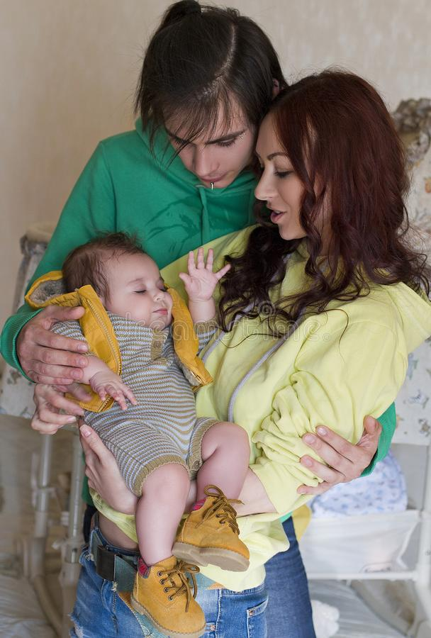 Young family mom, dad and son at home. Happy couple holding a baby. young neformal family with facial piercing. mom, dad and sleeping son at home royalty free stock image