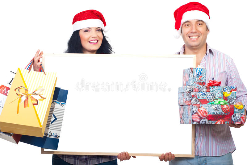 Happy couple holding banner and Xmas gifts. Happy smiling couple with Santa hats holding Christmas shopping bags and gifts boxes and a blank white banner stock photo
