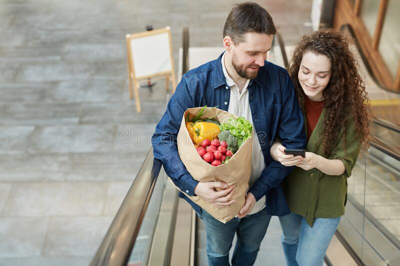 Happy Couple Holding Groceries on Escalator royalty free stock photos