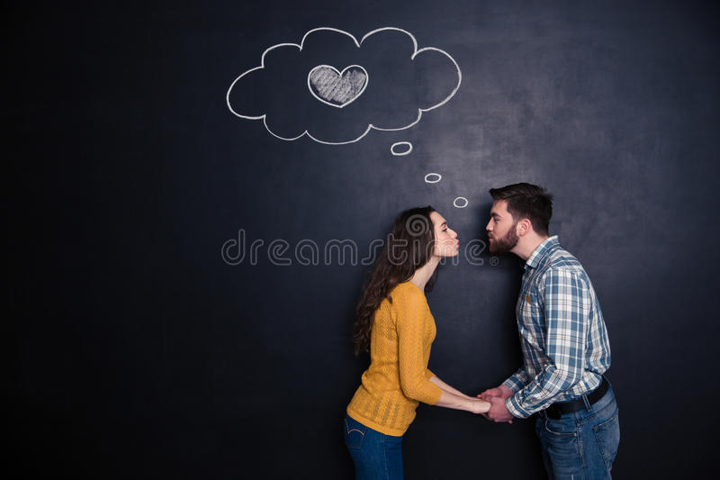 Happy couple holding hands and kissing over backboard background royalty free stock images