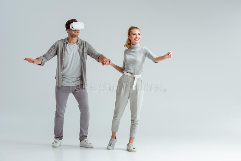 Happy couple holding hands while man experiencing virtual reality. On grey background stock photos