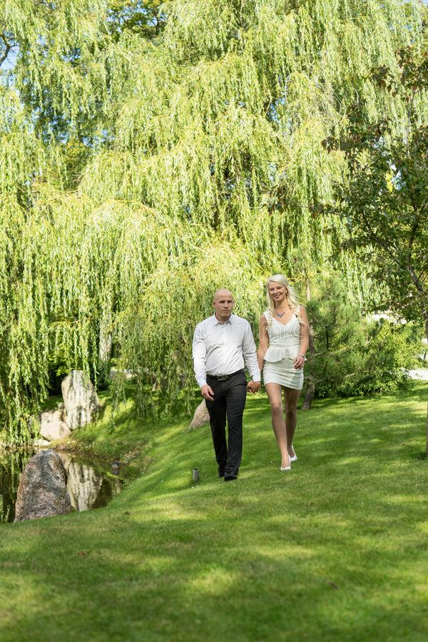 Happy couple holding hands and walking in grass. royalty free stock image