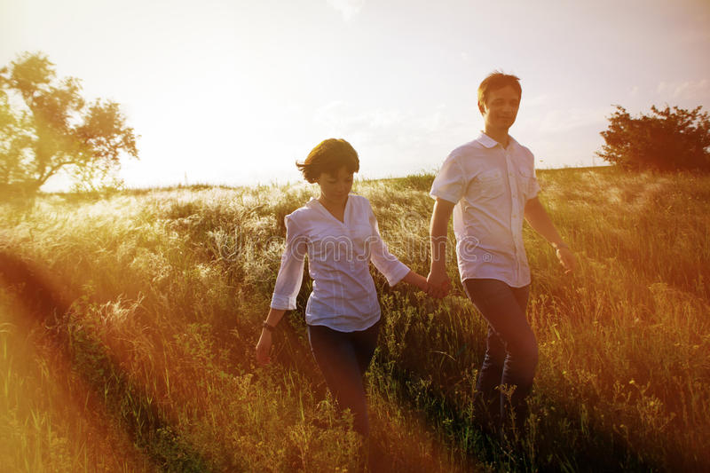 Happy couple holding hands walking through a meadow, tinted photo royalty free stock image