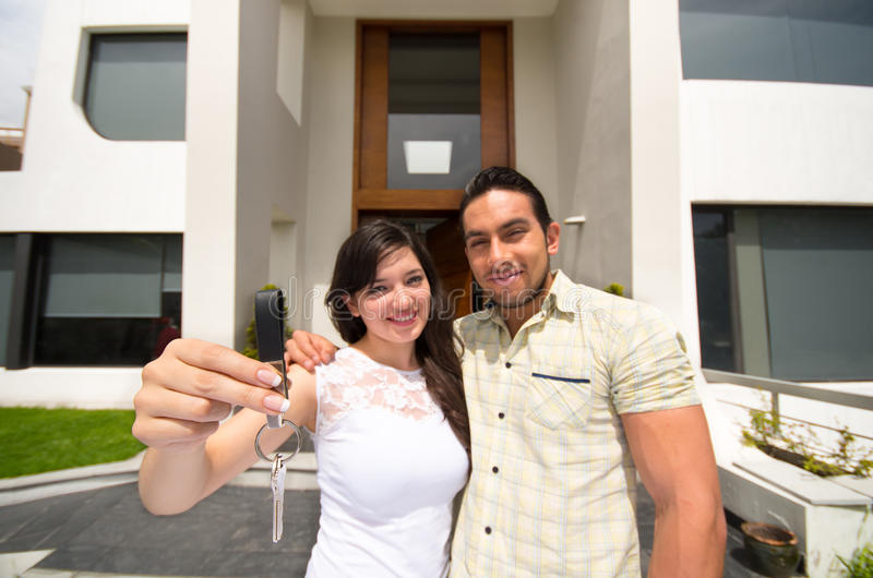 Happy couple holding key to their new house stock photography