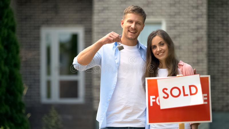 Happy couple holding keys from house near sold sign, mortgage for young families stock images