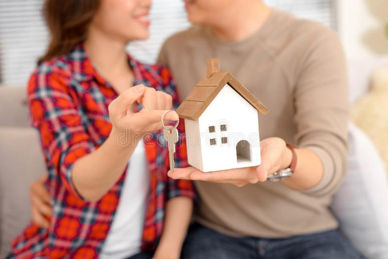 Happy couple holding keys to new home and house miniature - real royalty free stock image