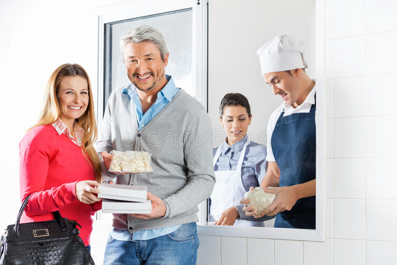 Happy Couple Holding Pasta Packets By Chefs At stock photos