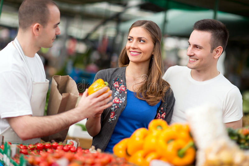 Happy couple holding pepper at a market stall. Happy couple holding yellow pepper at a market stall stock photography