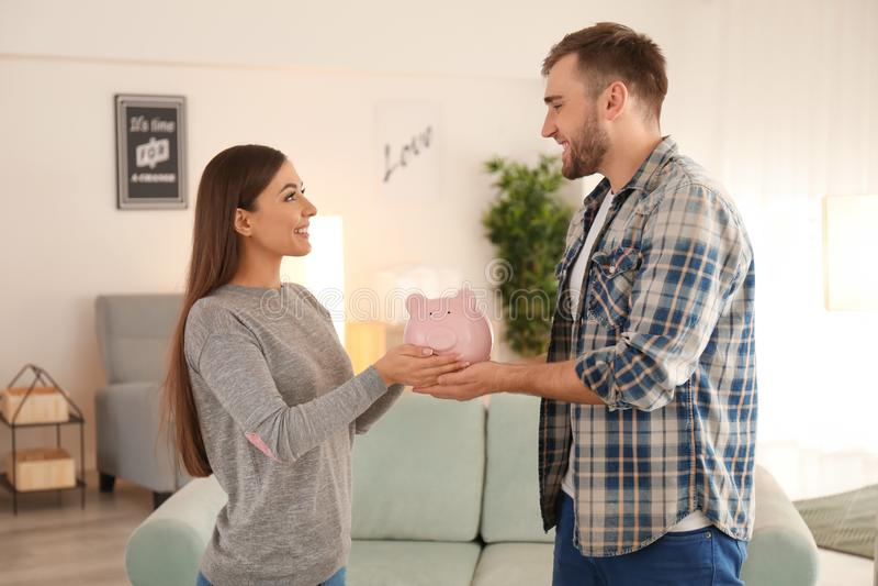 Happy couple holding piggy bank indoors. Money savings concept stock image