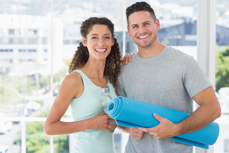 Happy couple holding water bottle and exercise mat at gym royalty free stock photos