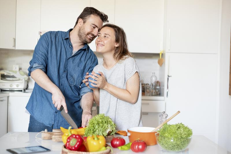 Portrait of young couple in love preparing food. Happy couple in home kitchen cooking together vegetables royalty free stock images