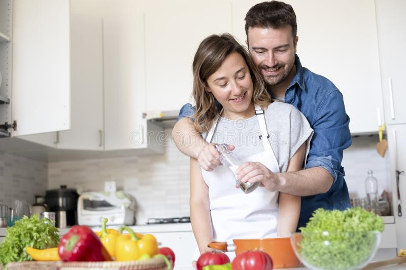 Happy couple in home kitchen cooking together vegetables. Portrait of young couple in love preparing food stock images