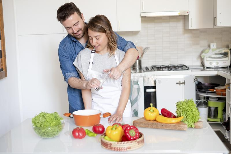 Happy couple in home kitchen cooking together vegetables. Portrait of young couple in love preparing food royalty free stock photos