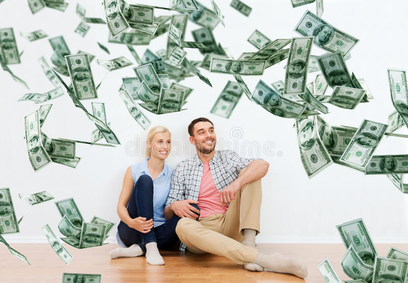 Happy couple at home over dollar money falling. Home, people, moving, finances and real estate concept - happy couple of men and women sitting on floor and stock photography