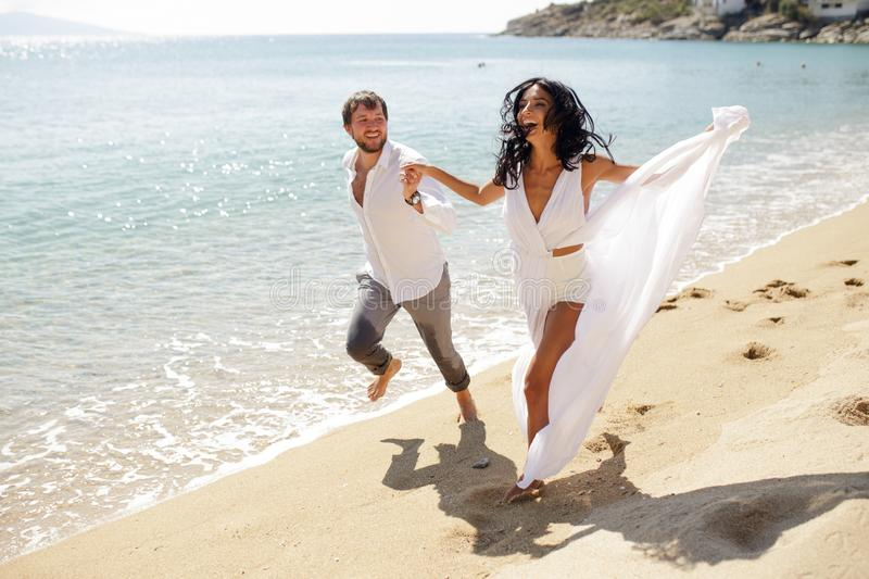 Happy couple in honeymoon on Greece, smiling and run on the beach, summer time, sunny day. stock photography