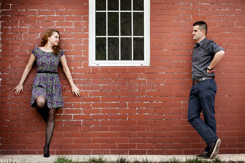 Happy couple and house with brick wall. Happy young couple and house with brick wall stock photo