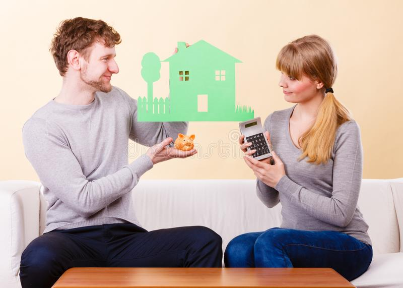 Happy couple with house and calculator. stock image