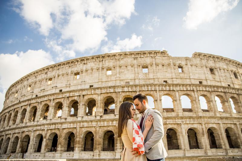 Happy couple hugging in front of Colosseum in Rome, Italy royalty free stock image