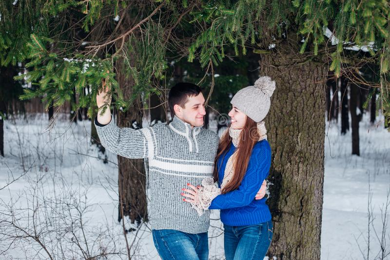 Happy couple hugging and laughing outdoors in winter forest royalty free stock photography
